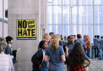 Students standing in hallway next to no place for hate sign